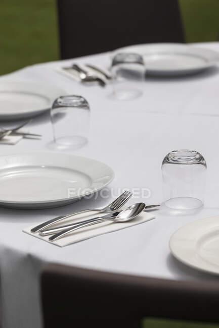 Coloque los ajustes en la mesa de comedor redonda - foto de stock