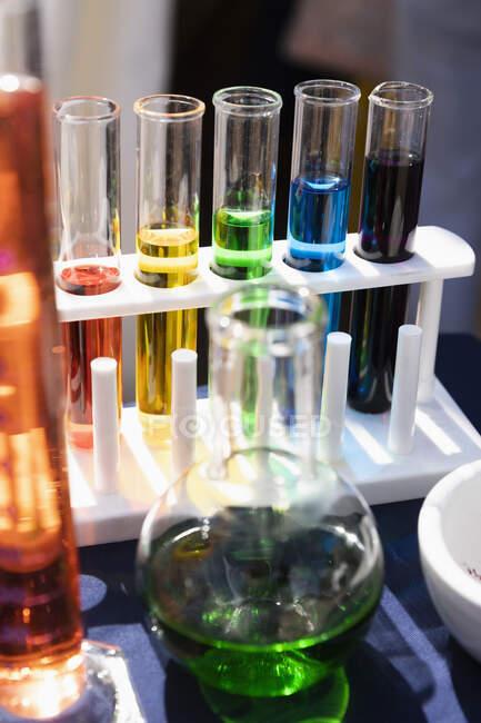 Liquide multicolore dans le support et le bécher des éprouvettes — Photo de stock
