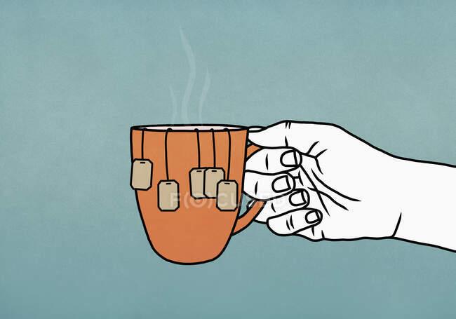 Рука держа кружку со многими пакетиками чая — стоковое фото