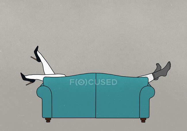 Legs of couple dangling over sofa — Stock Photo