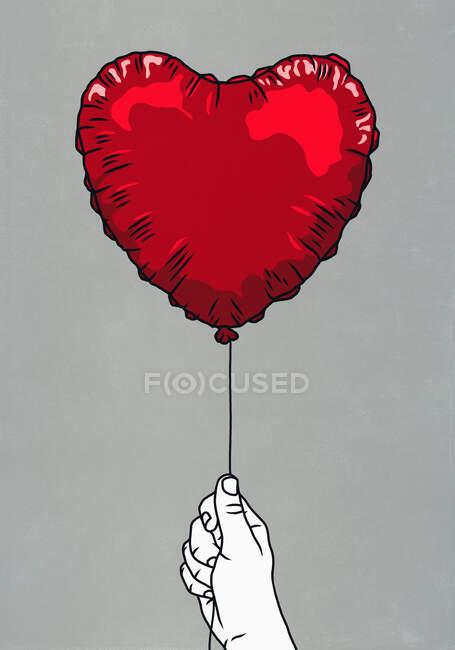 Hand holding red heart shape balloon — Stock Photo