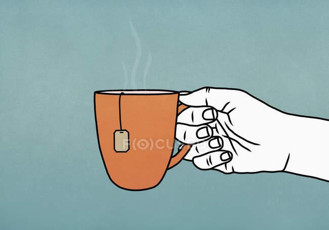 Hand holding mug of hot tea — Stock Photo