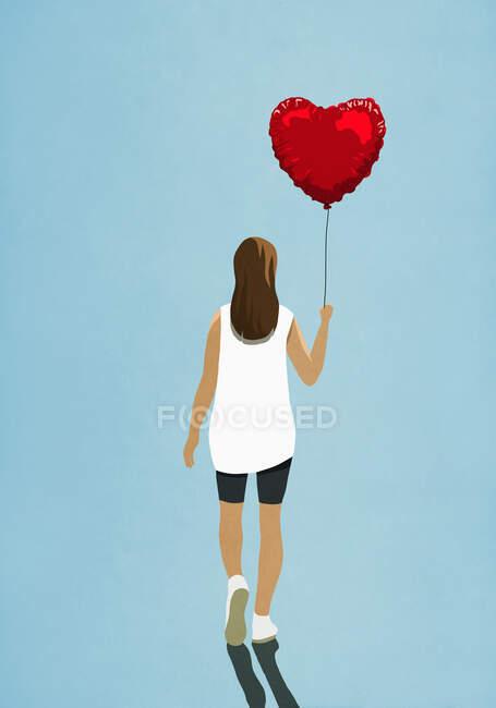Женщина с гелиевым шаром в форме сердца — стоковое фото