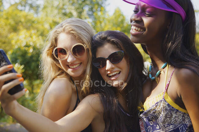 Happy teenage girl friends taking selfie with smart phone on sunny patio — Stock Photo