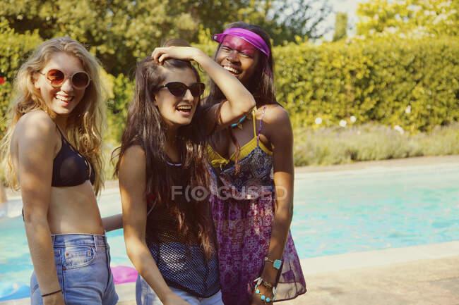 Ritratto felice ragazza adolescente amici a soleggiata estate a bordo piscina — Foto stock