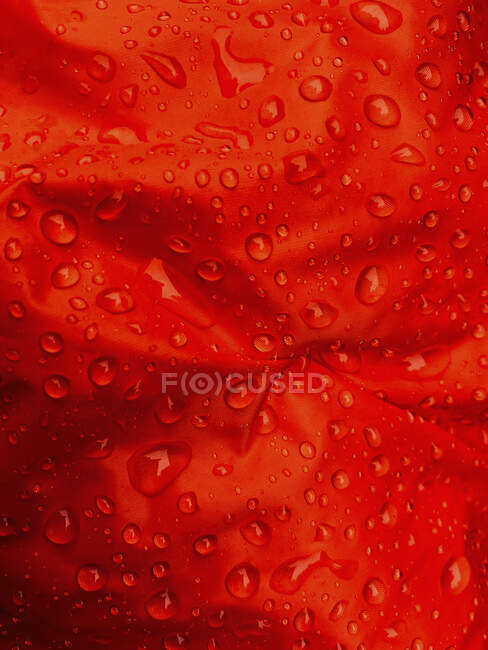 Close up water droplets on red fabric — Stock Photo