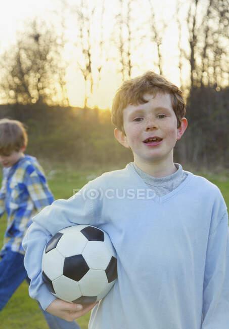 Портрет мальчика с веснушками, держащего футбольный мяч в парке — стоковое фото
