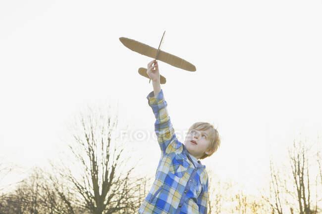 Niño jugando con el avión de cartón en el parque - foto de stock