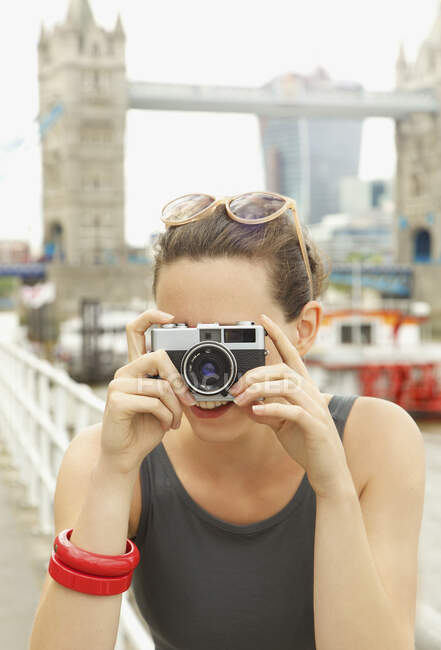 Portrait young woman with retro camera in front of Tower Bridge, London — Stock Photo