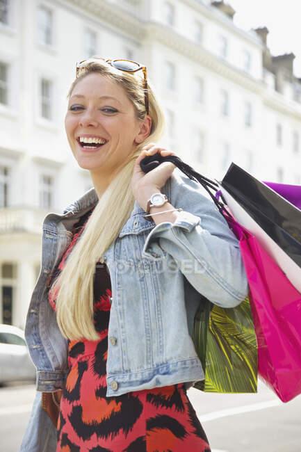 Портрет счастливой молодой женщины с сумками для покупок на солнечной городской улице — стоковое фото