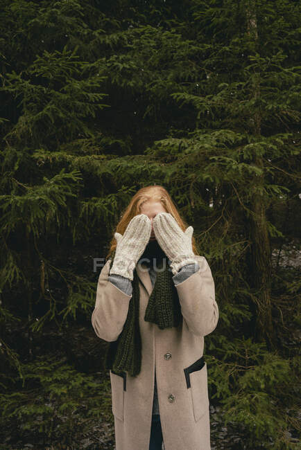 Portrait playful woman with mittens covering face in woods — Stock Photo