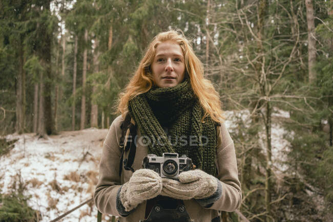 Portrait redhead woman with camera in snowy woods — Stock Photo