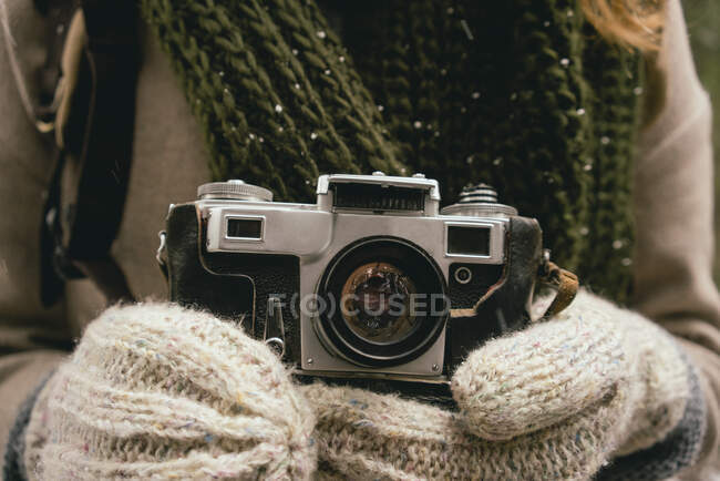 Close up woman in mittens holding retro camera — Stock Photo