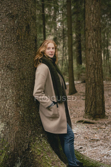 Portrait confident redhead woman in wool coat leaning against tree in woods — Stock Photo