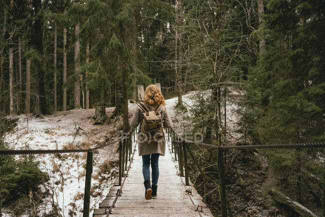 Redhead woman with backpack on footbridge in snowy woods — Stock Photo
