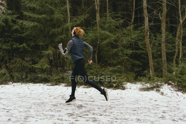Woman running in snowy woods — Stock Photo