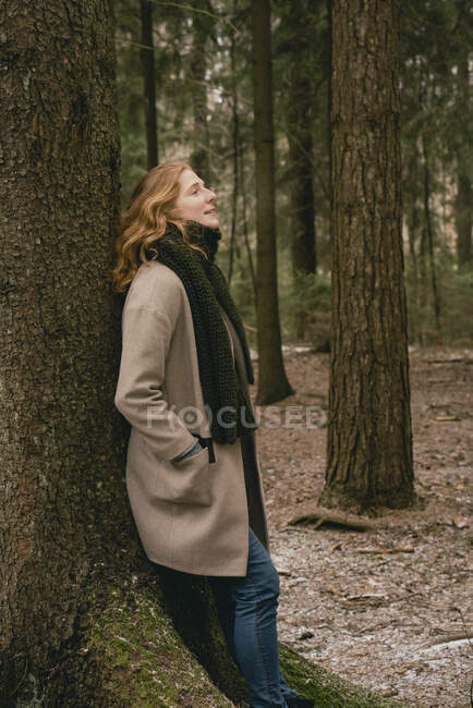 Serene redhead woman in wool coat and scarf leaning against tree in woods — Stock Photo