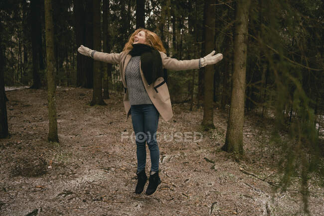 Carefree woman jumping for joy in woods — Stock Photo