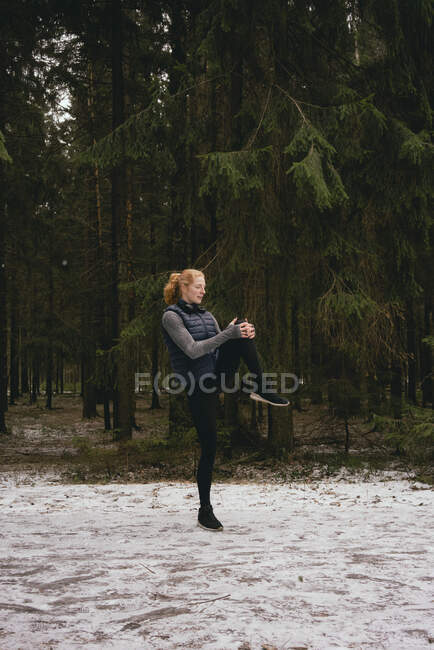 Female runner stretching legs in snowy woods — Stock Photo