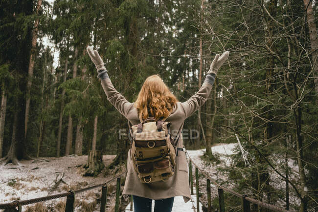 Carefree woman with backpack standing with arms outstretched on footbridge in woods — Stock Photo