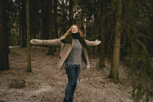 Exuberant, carefree woman with arms outstretched in woods — Stock Photo