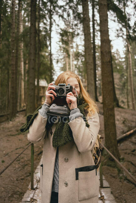 Portrait woman using retro camera in woods — Stock Photo