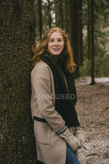 Portrait confident redhead woman in scarf and wool coat leaning against tree in woods — Stock Photo