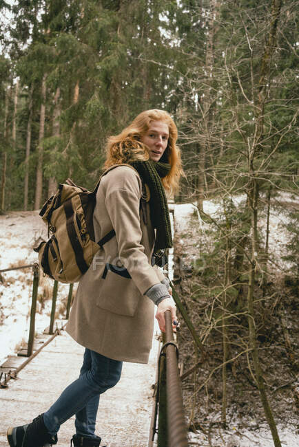 Portrait redhead woman with backpack on footbridge in snowy woods — Stock Photo