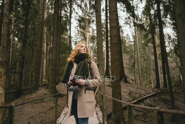 Serene redhead woman with camera on footbridge in woods — Stock Photo