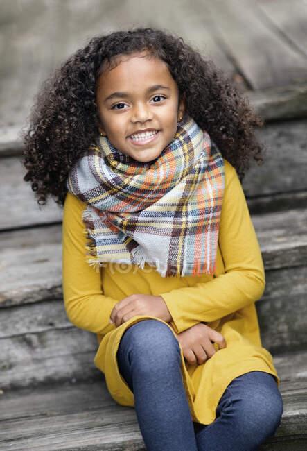 Портрет щасливої дівчини в шарфі на дерев