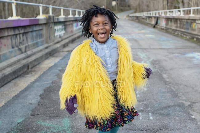 Портрет щаслива дівчина в жовтій нечіткій куртці на мосту — стокове фото
