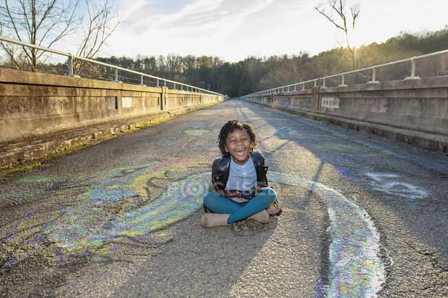 Портретна щаслива дівчина сидить серед графіті на сонячному мосту. — стокове фото
