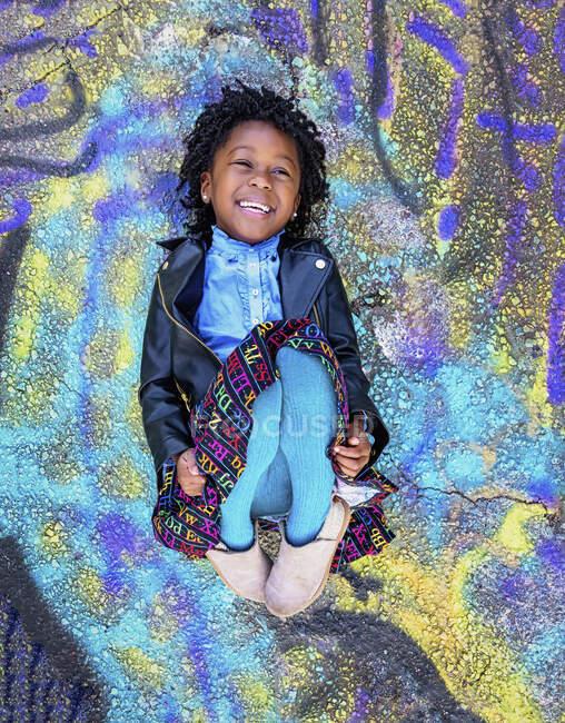Портретна щаслива дівчина лежить у графіті. — стокове фото
