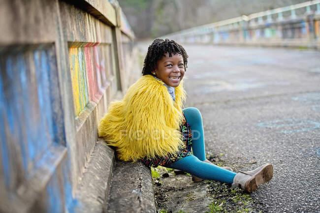 Портрет щаслива дівчина в жовтій пухнастій куртці на мосту — стокове фото