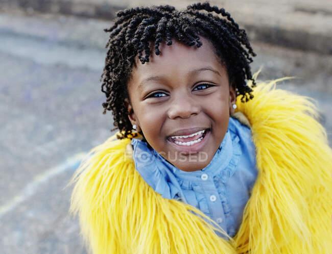 Портретна щаслива дівчина в жовтій пухнастій куртці — стокове фото