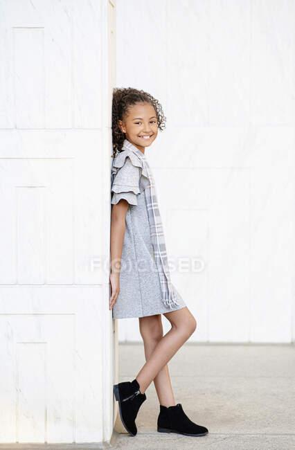 Retrato de chica sonriente y confiada en vestido y botines de pie en la pared - foto de stock