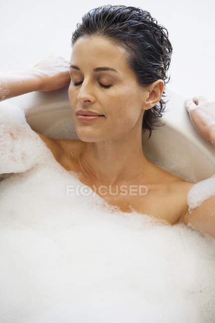 Serene woman enjoying bubble bath — Stock Photo