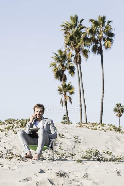 Босоногий бизнесмен с цифровым планшетом и смартфоном работает на солнечном пляже — стоковое фото