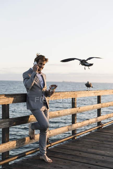 Empresário descalço falando em telefone inteligente no cais ensolarado, Los Angeles, Califórnia — Fotografia de Stock