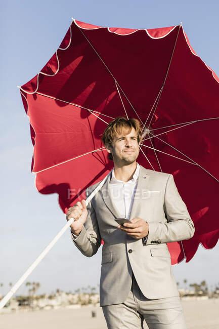 Бизнесмен с пляжным зонтом на солнечном пляже — стоковое фото