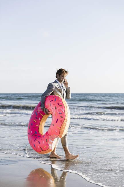 Empresário com donut inflável na praia ensolarada do oceano, Los Angeles, Califórnia — Fotografia de Stock