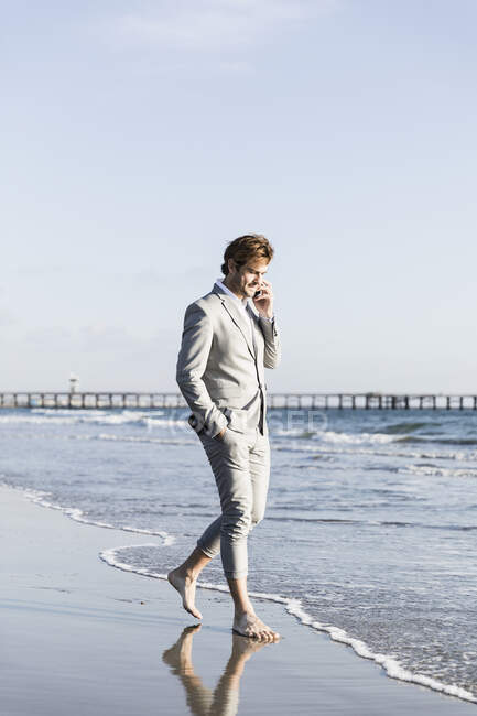 Empresário descalço falando em telefone inteligente na praia ensolarada do oceano, Los Angeles, Califórnia — Fotografia de Stock