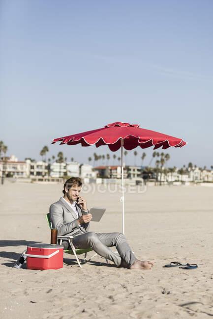 Empresário descalço com smartphone e tablet digital trabalhando na praia, Los Angeles, Califórnia — Fotografia de Stock