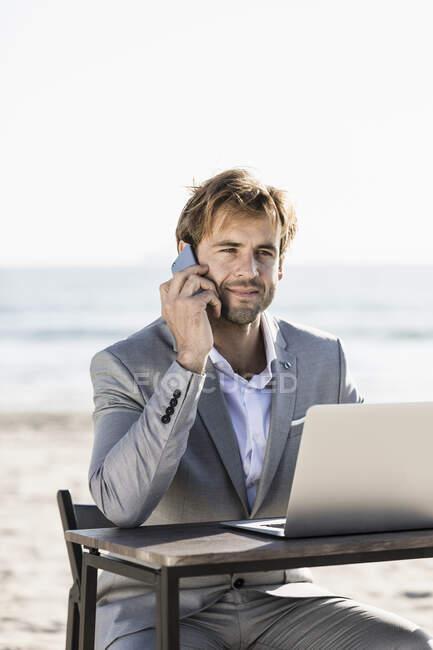 Бизнесмен со смартфоном и ноутбуком работает на солнечном пляже — стоковое фото