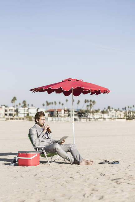 Бизнесмен с цифровым планшетом работает на солнечном пляже, Лос-Анджелес, Калифорния — стоковое фото