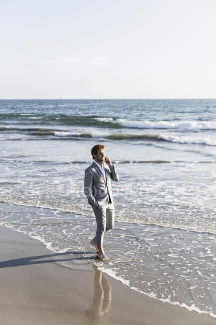 Босоногий бизнесмен разговаривает по смартфону в солнечном океане, Лос-Анджелес, Калифорния — стоковое фото