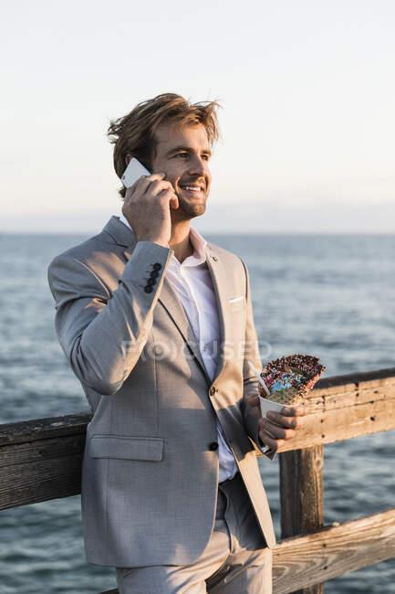 Empresário com cone de sorvete falando em telefone inteligente no cais oceânico — Fotografia de Stock