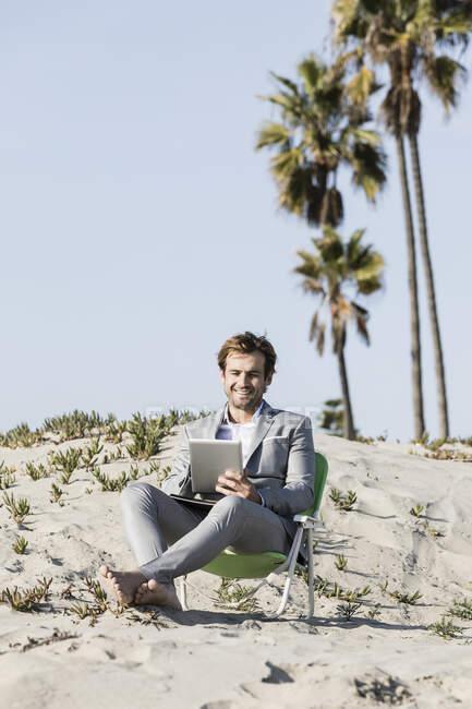 Barefoot бизнесмена, использующего цифровой планшет на солнечном пляже, Лос-Анджелес, Калифорния — стоковое фото