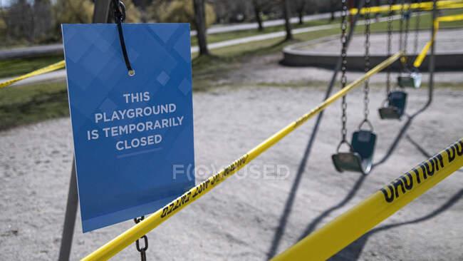 Aire de jeux fermée signe et ruban adhésif pendant la pandémie COVID-19 — Photo de stock