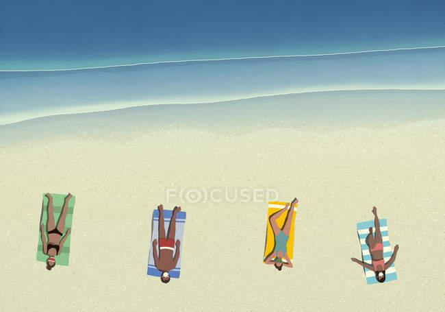 Pessoas em máscaras de rosto protetoras banhos de sol e distanciamento social na praia ensolarada — Fotografia de Stock